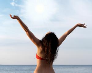 The girl on seacoast greeting sun